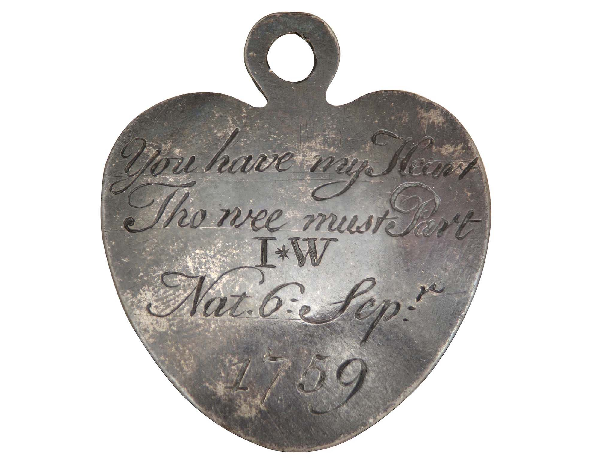 a photo of a heart shaped token with an inscription on it