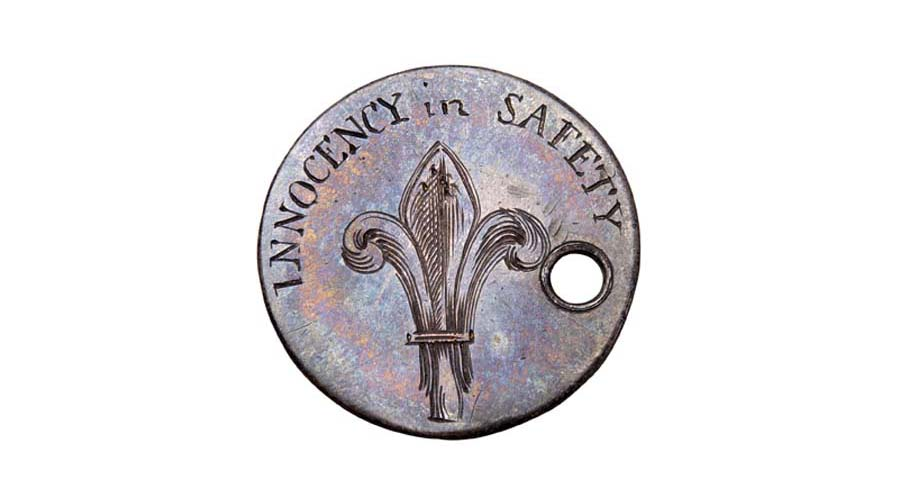 a photo of a round token with a fleur de lis and the words innocency in safety
