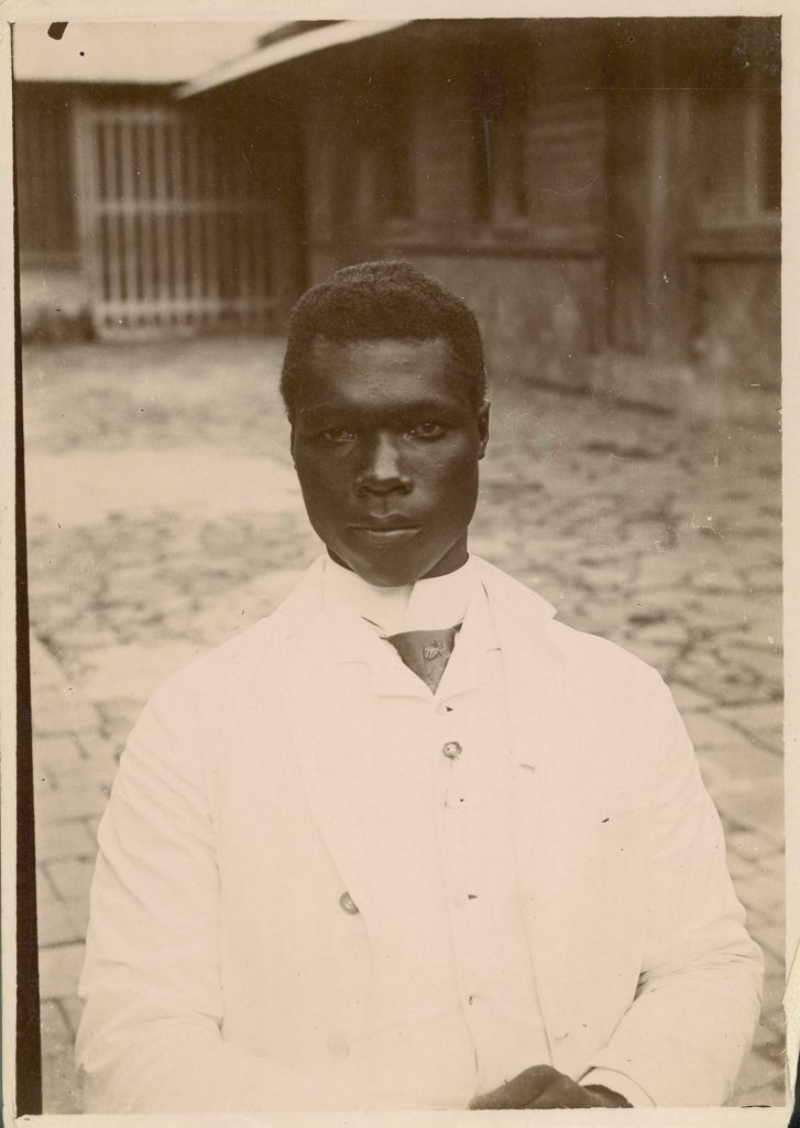 A photo of a young black man wearing a white suit