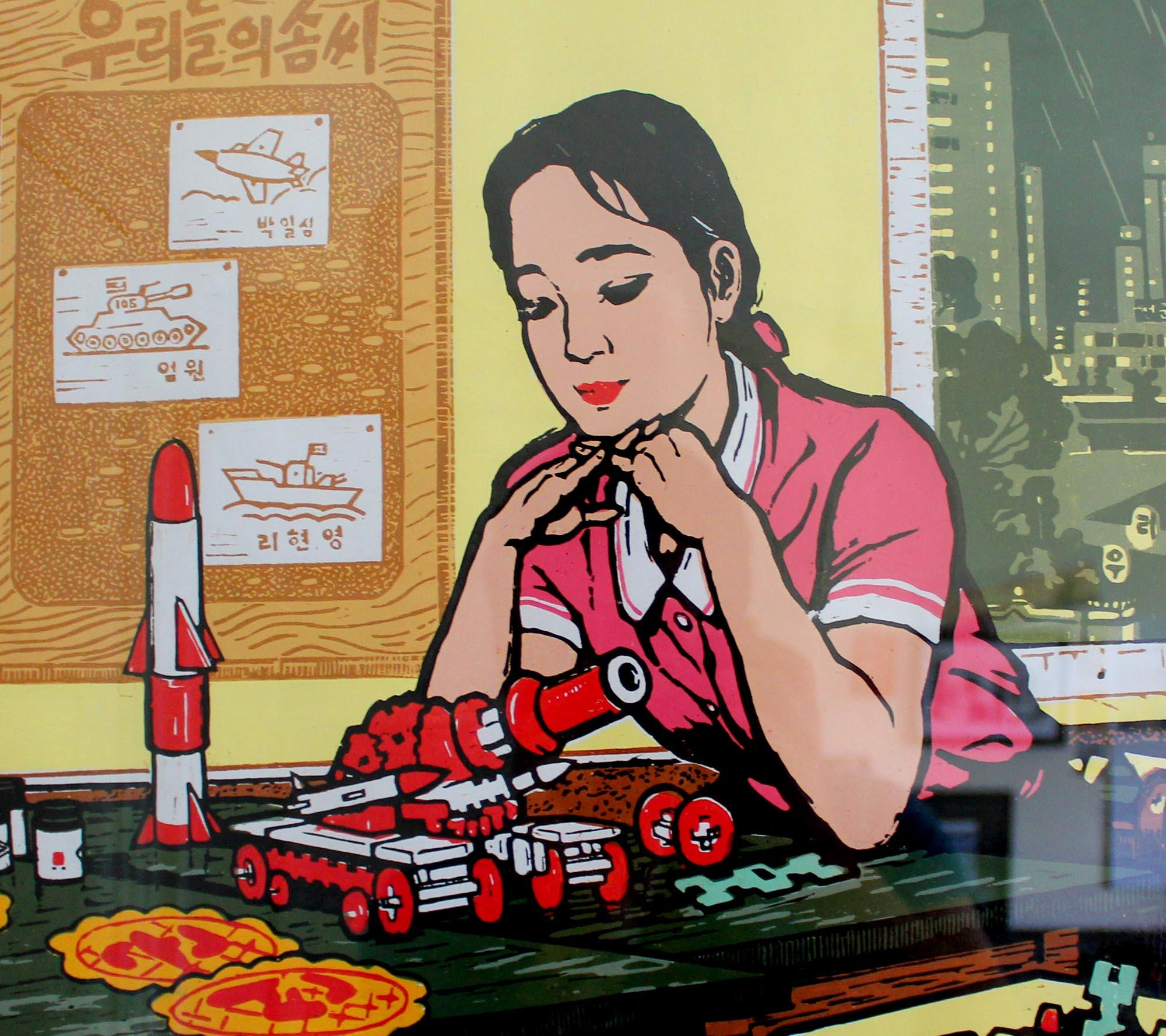 a North Korean propaganda poster showing a girl looking at models of missiles