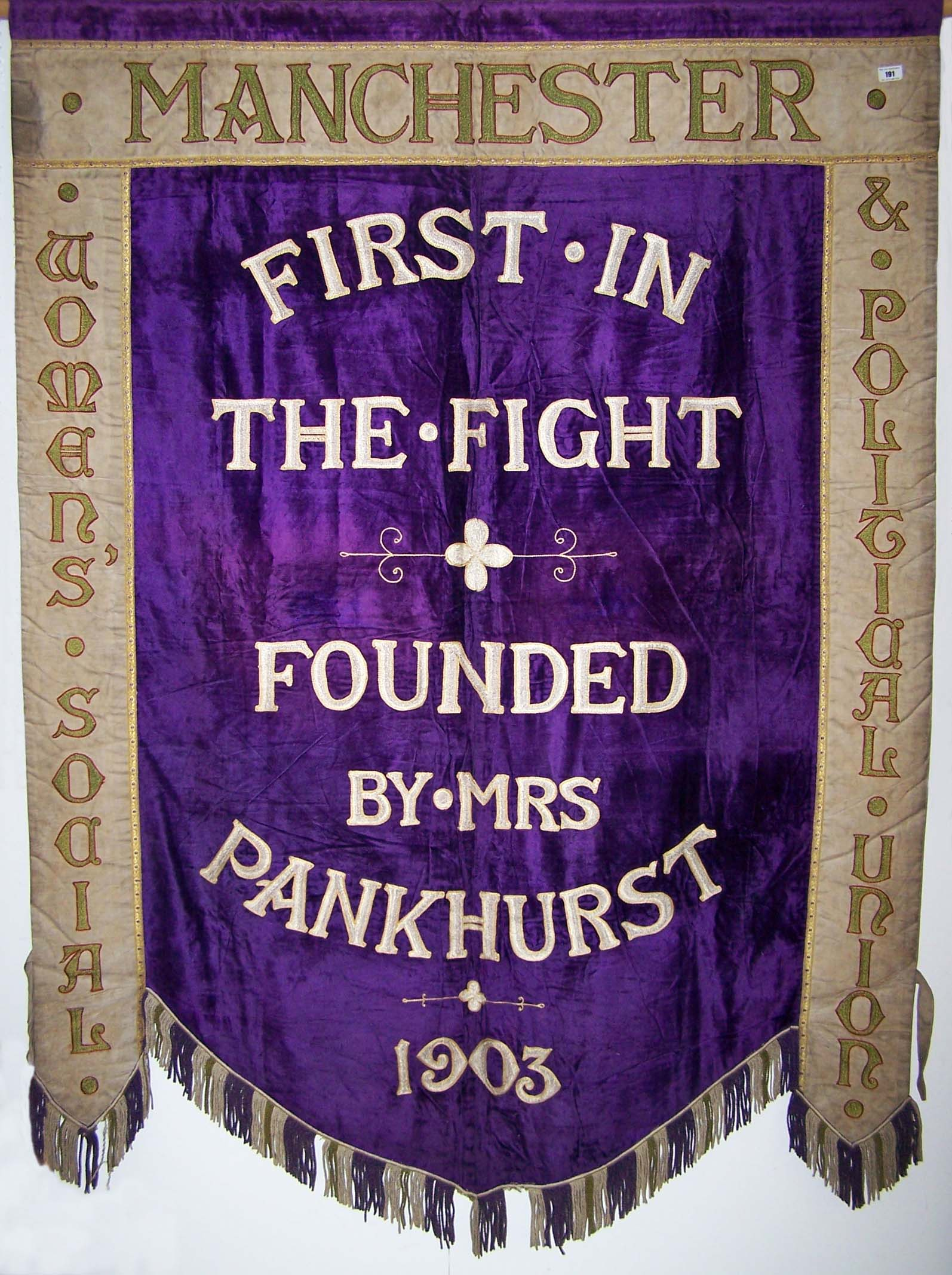 a photo of a purple banner with thee words First in the Fight Founded by Mrs Pankhurst 1903.