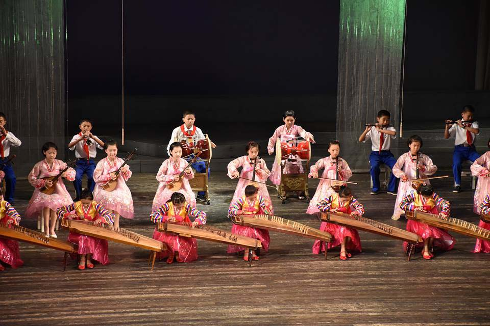 a photo of a group of traditionally dressed North Korean playing instruments on stage