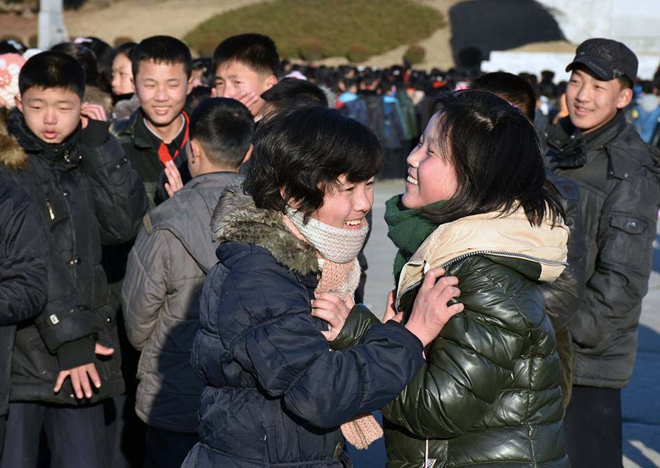 a photo of two North Korean teenage girls laughing in a crowd