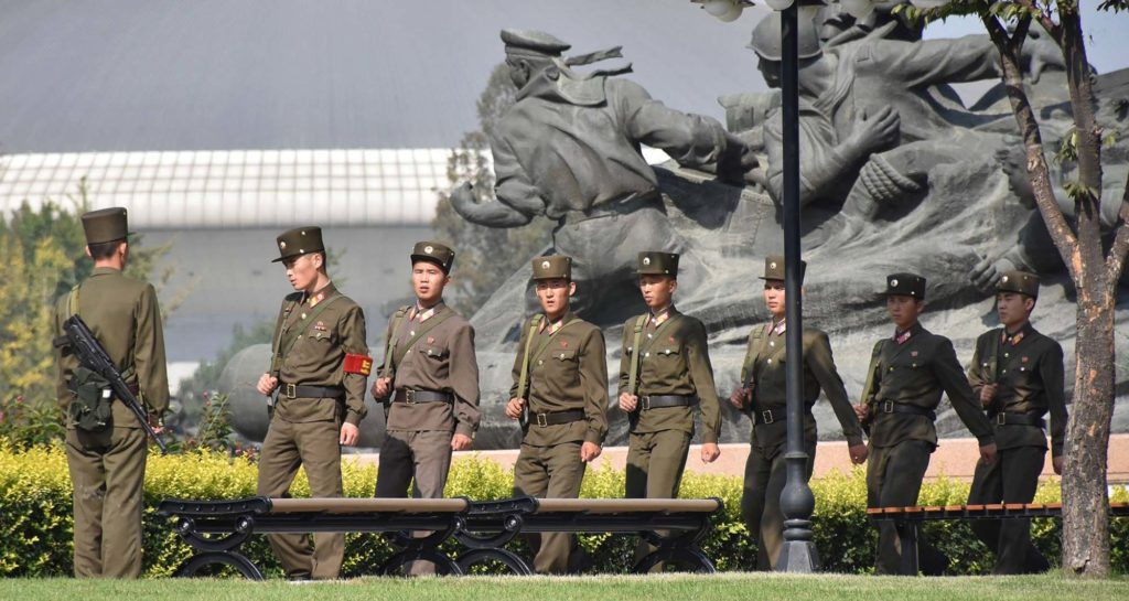 a photo of a group of North Korean soldiers walking past a large statue