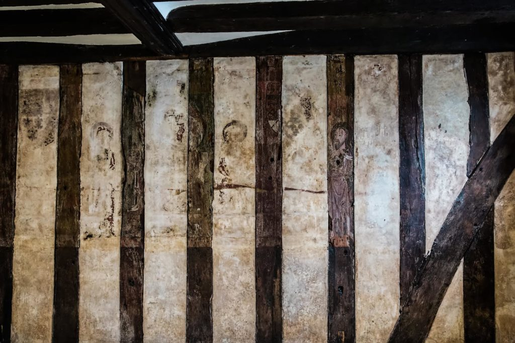 a photo of a stud wall with beams and the outline of a painting visible on it