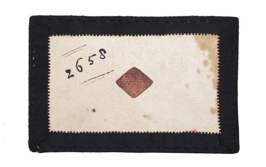 a photo of an old playing card with a red diamond at its centre