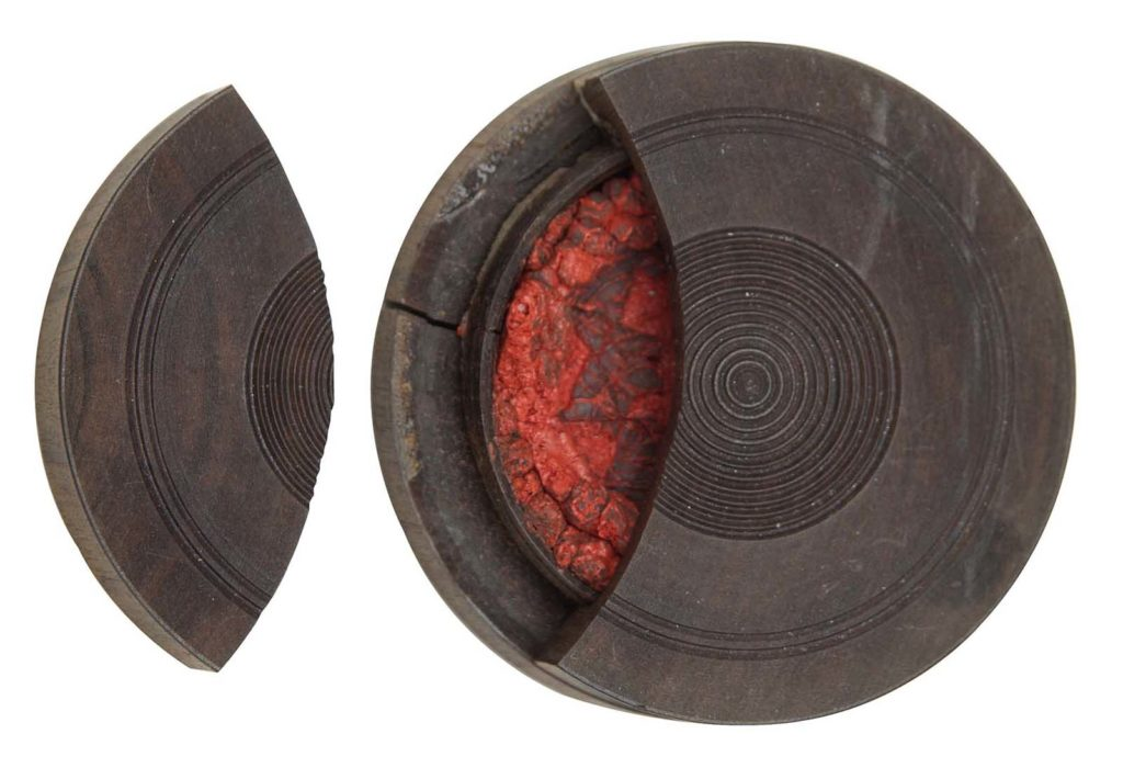 a photo of a pot with a broken lid and rouge visible inside