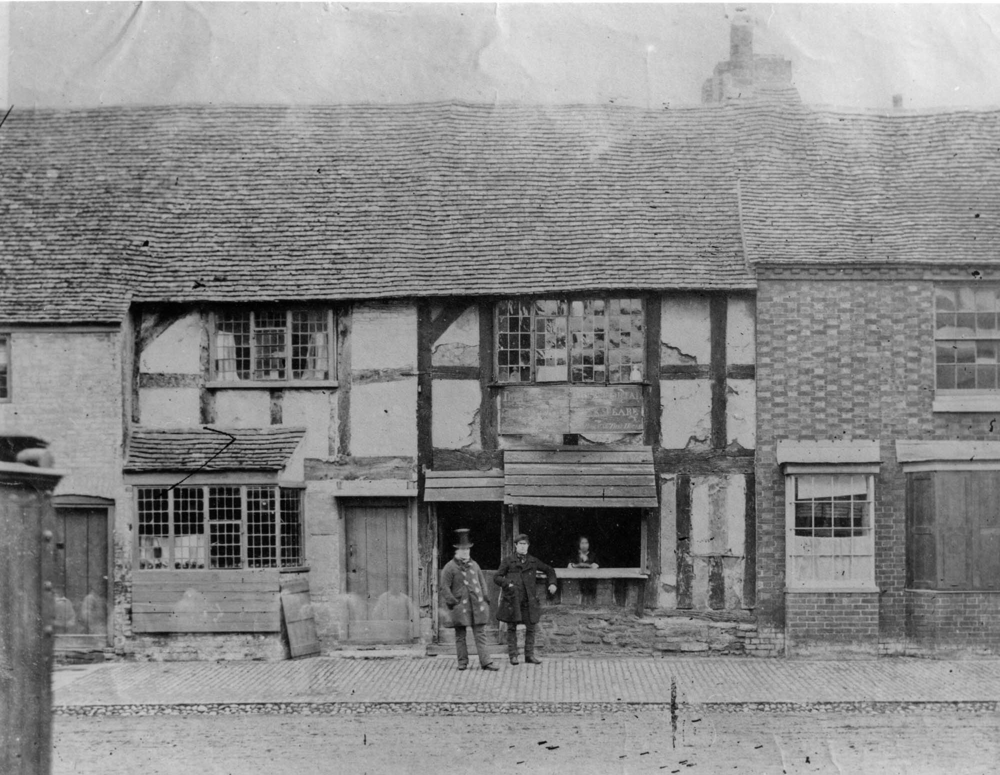 an old black and white photo of timber framed building with two Victorian men in the foreground - one wearing a top hat