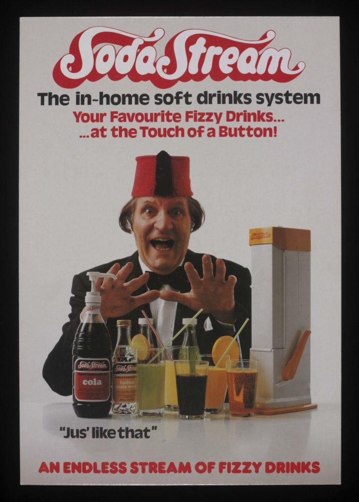 a advertisement featuring Tommy Cooper with his fez grinning next to a drinks making machine