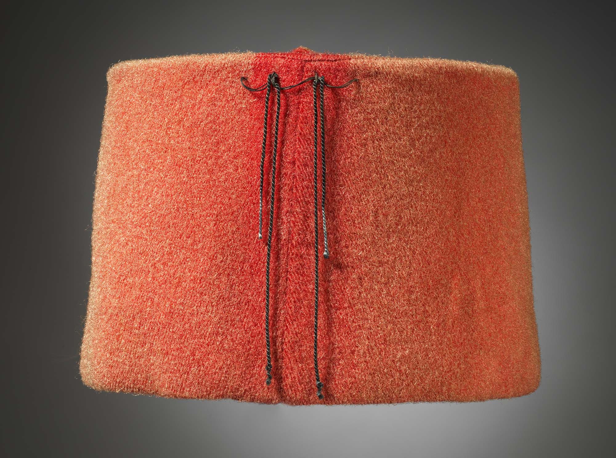 a photo of a red fez with a couple of tassels