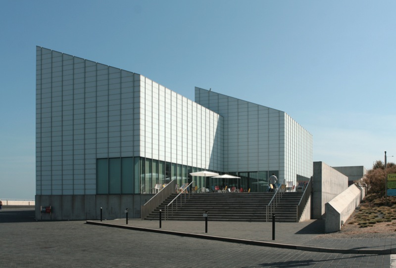 A photo of the exterior of the building, two large rectangular buildings both with a slanted roof
