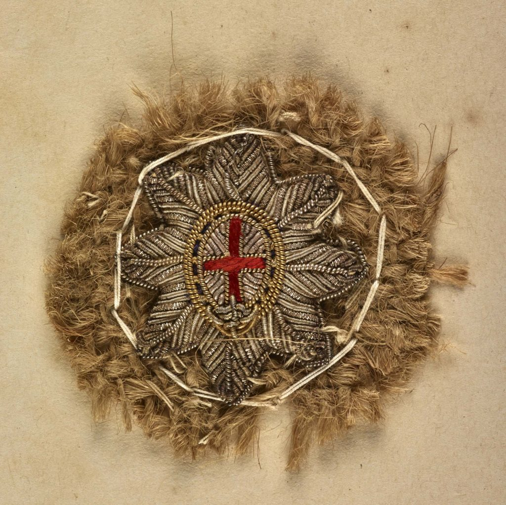 a photo of a crudely woven badge with a star and cross at its centre