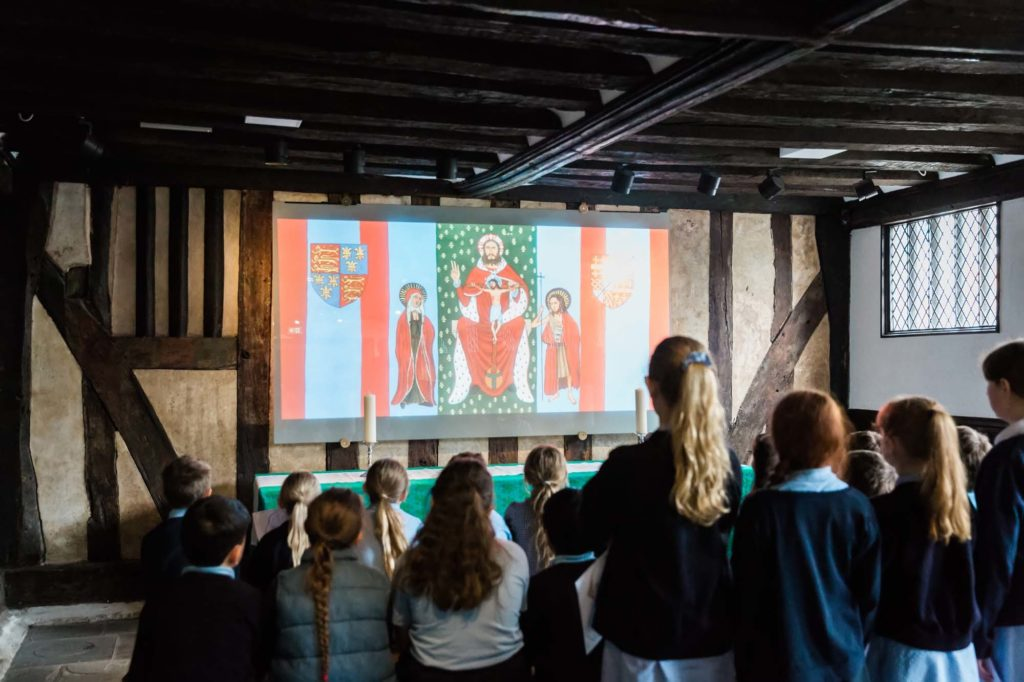a photo of a group of schoolchildren looking towards a panel with a medieval religious painting on it