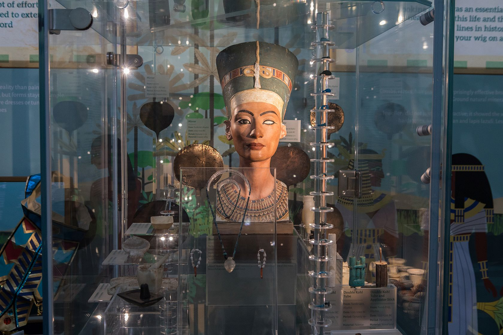 photograph of ancient egyptian bust of woman in display case with other encient egpytian artefacts