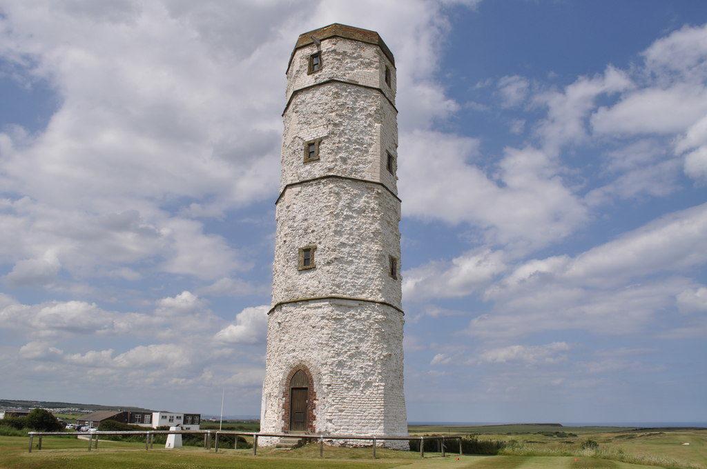 photograph of 17th century lighthouse against a blue cloudy sky