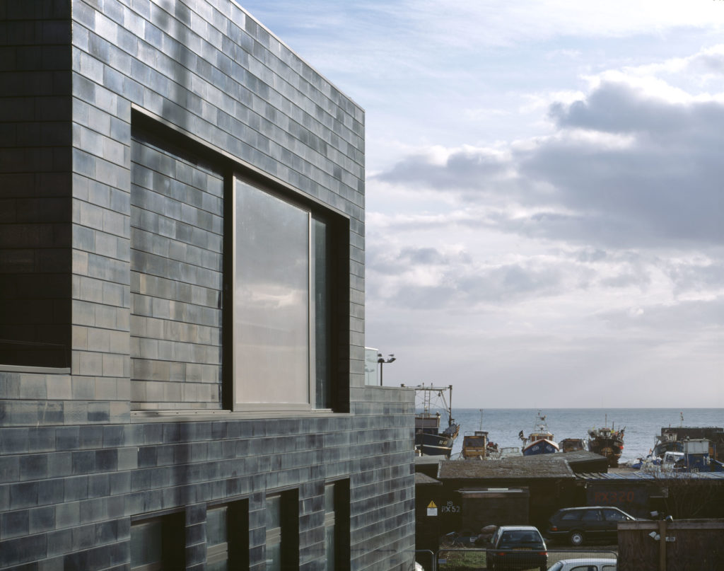 photograph of exterior of modern tiled building, facing the sea