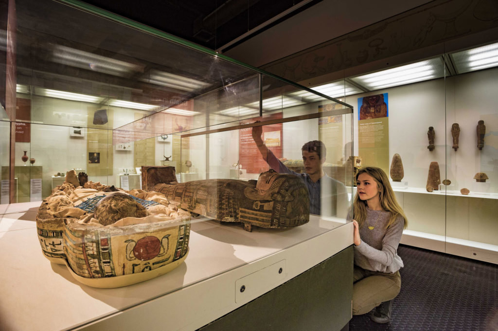 photograph of girl and boy crouching by a display case containing a mummy and sarcophagus
