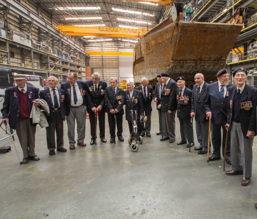 a photo of a group of old veterans in blazers and berets standing in a large warehouse next to the rusting hulk of a a large craft