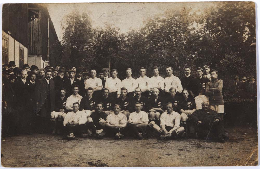 an old photograph of the England football team on the lawn of house surrounded by men with suits, moustaches and hats