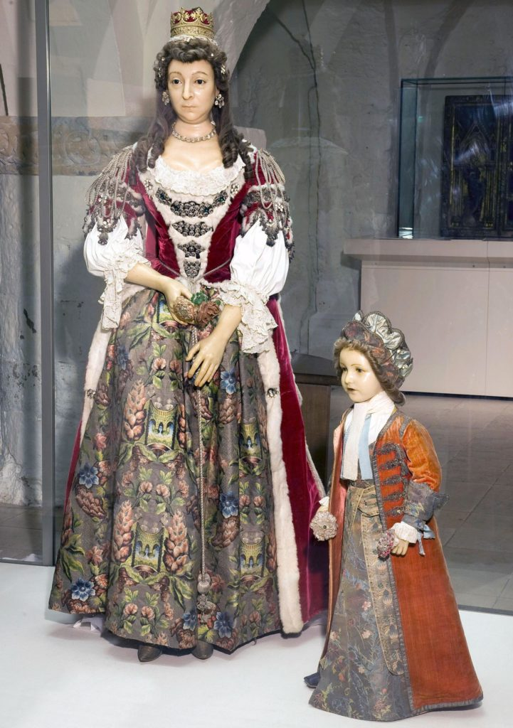 a photo of a full sized wax effigy of a woman in regal dress and young boy in a long frock coat