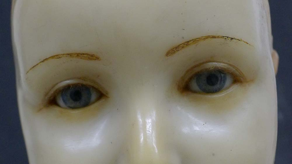 a closeup of the wax face and glass eyes of an effigy of a young boy