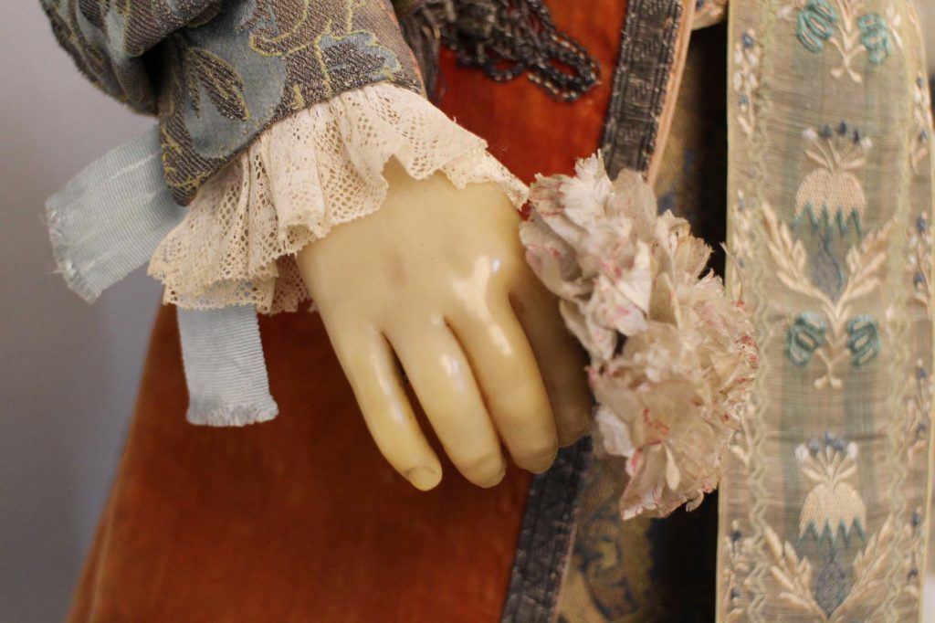 a close up of a waxed hand in a frilled cuff