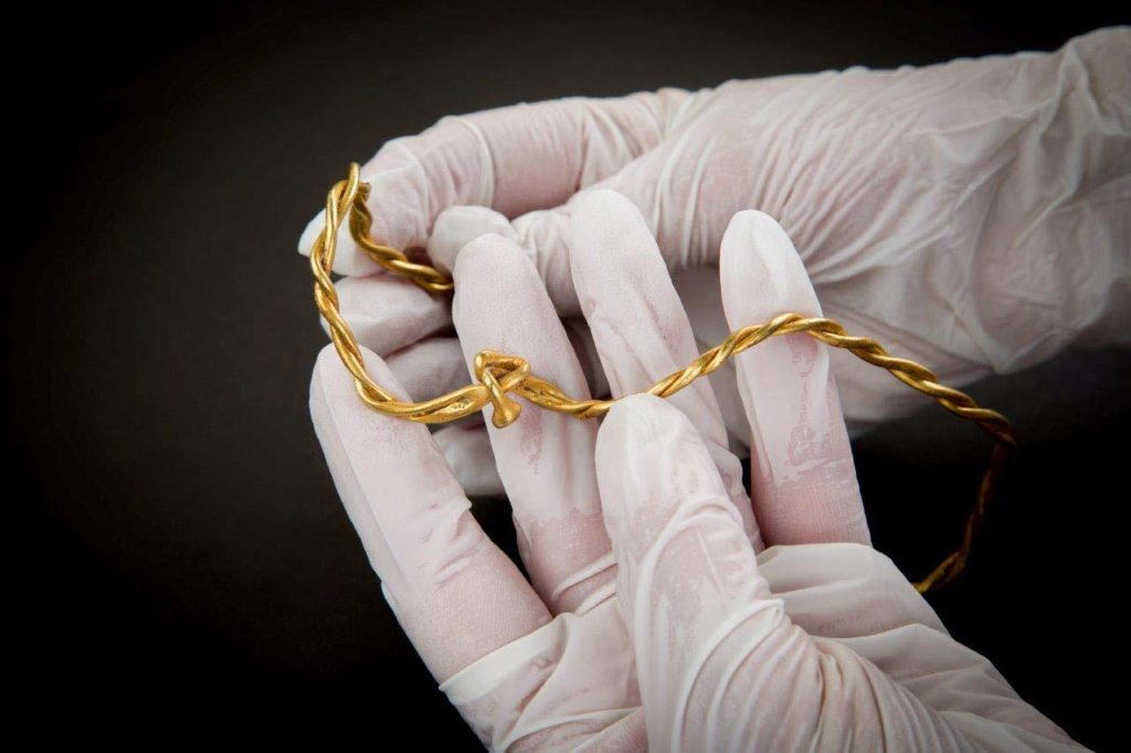 a photo of twisted golden wire work jewelry held in the gloved hand of a curator