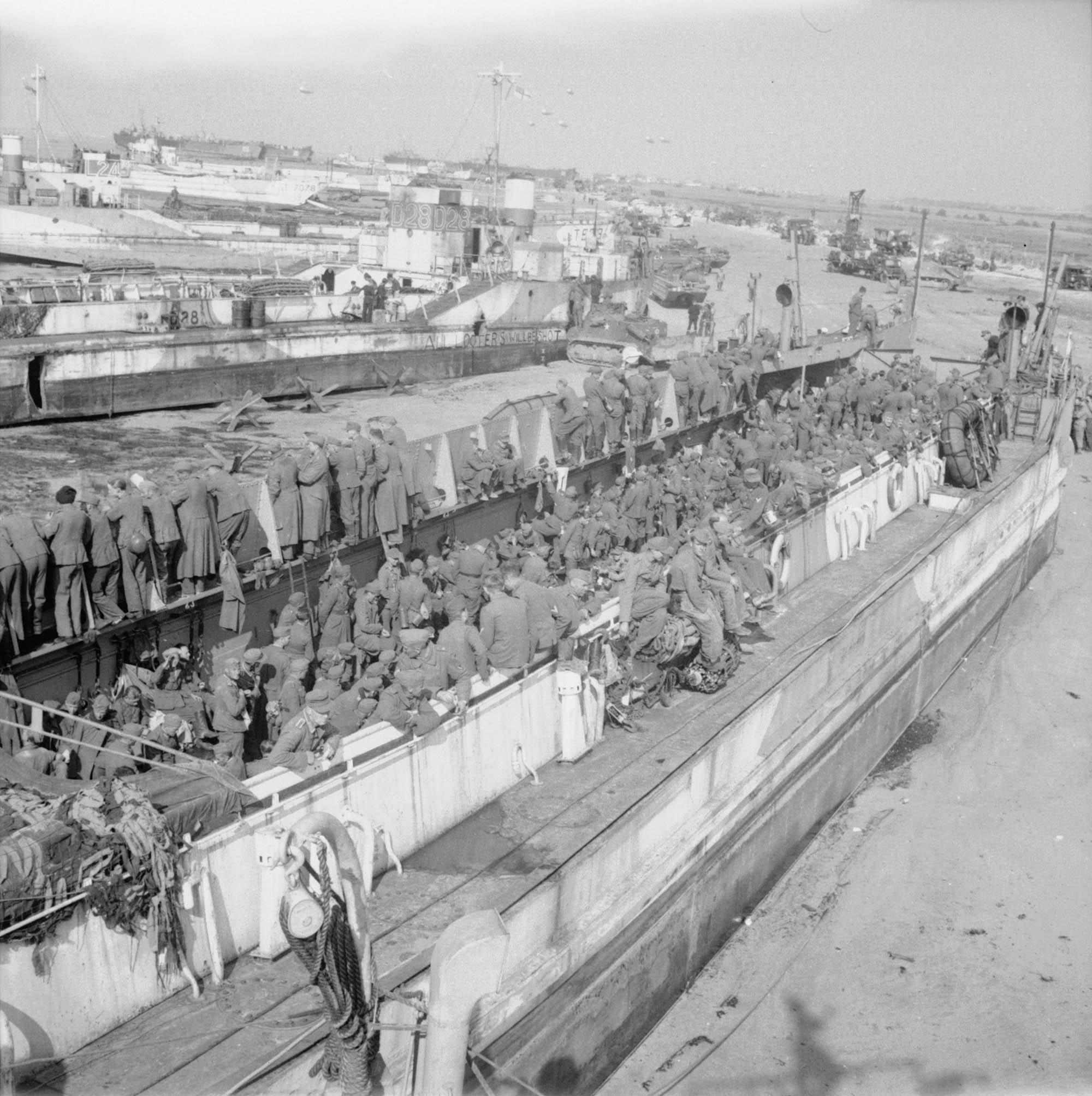 a black and white photo of lots of soldeirs standing on a large barge-like boat on a beach