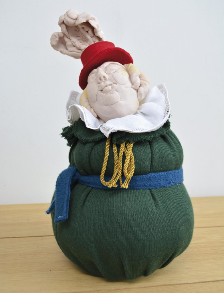 a photo of a sculpture of a green bag with a head protruding from it