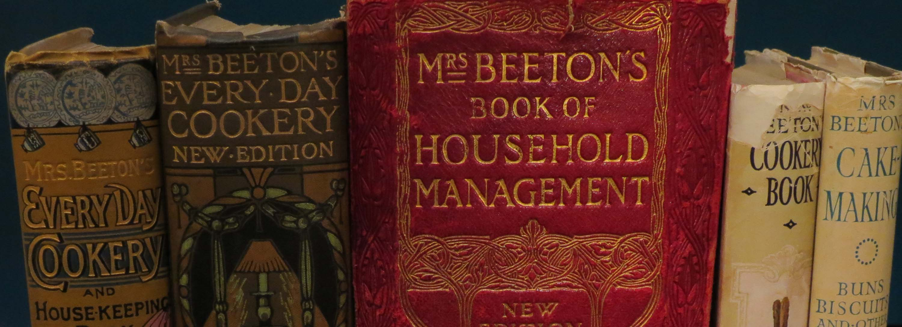 a photo of the spines of various copies of Mrs Beeton's Book of Household Management