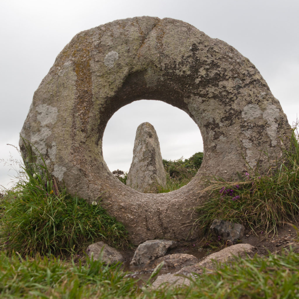 photograph of thin standing stone seen through a circular standing stone with hole through the middle