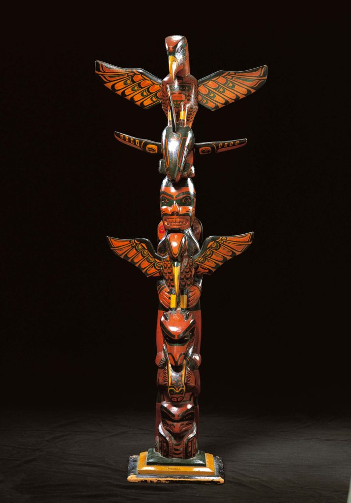Model of a totem pole, from the Northwest Coast of the USA, depicting a number of anthropomorphic and zoomorphic figures.