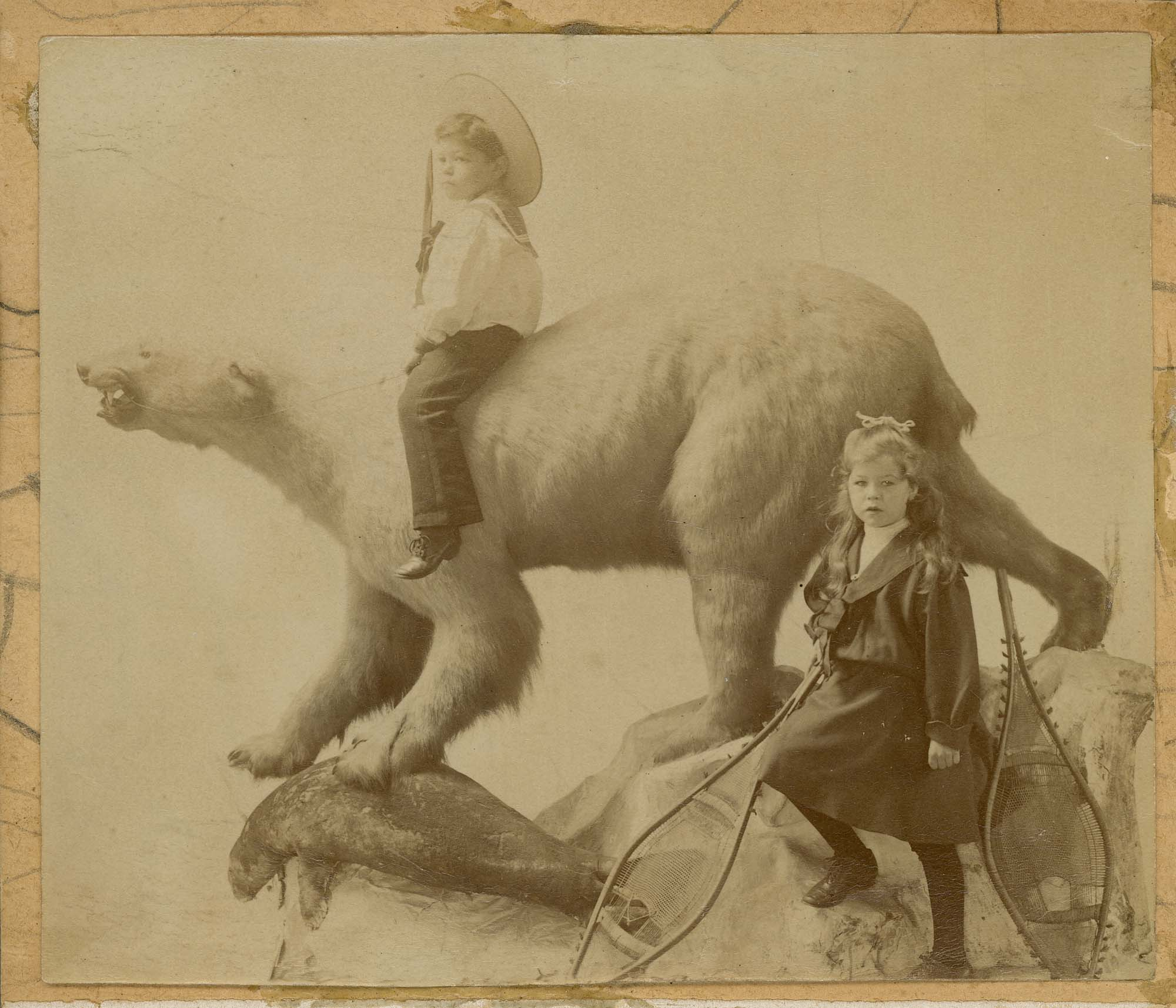 a black and white photo of tow Edwardian sailor suit and straw boater children riding a stuffed polar bear