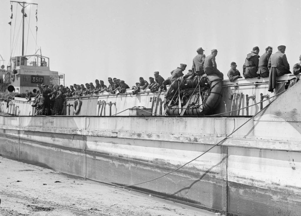 a black and white photo of a landing craft on beach with soldiers sitting on its side