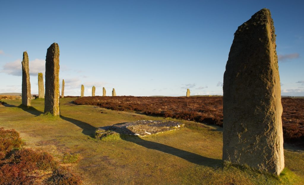 photograph of tall standing stones casting long shadows