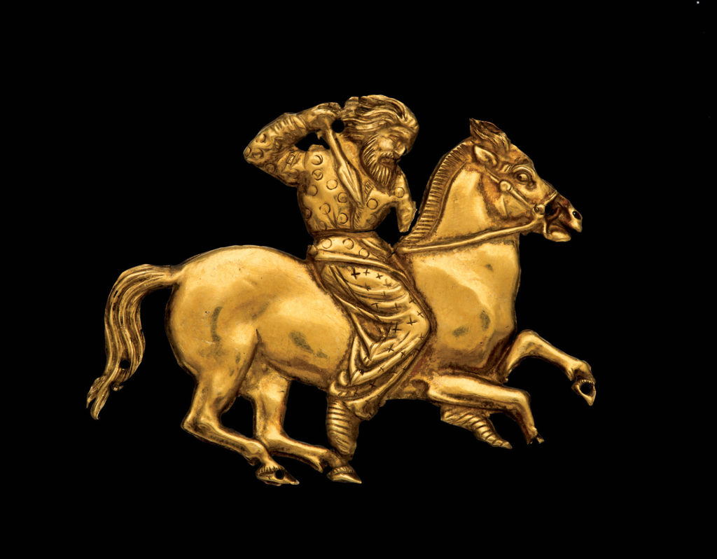 photograph of gold plaque showing man riding horse