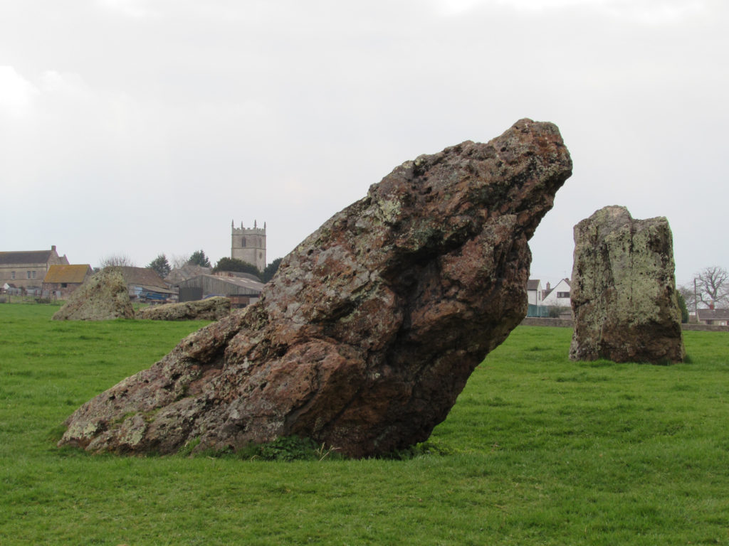 photogrpah of large standing stone emerging from grassy field