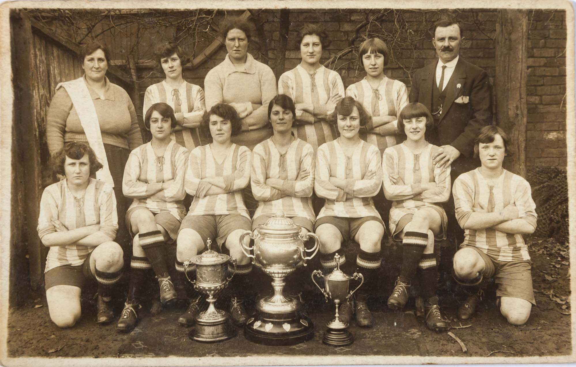 a black and white photo of a team of women footballers in striped kits with their male manager back left