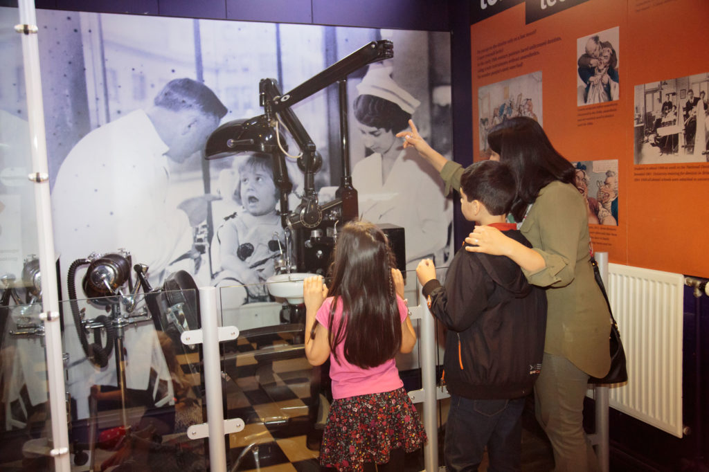 photograph of family looking at exhibit in a museum