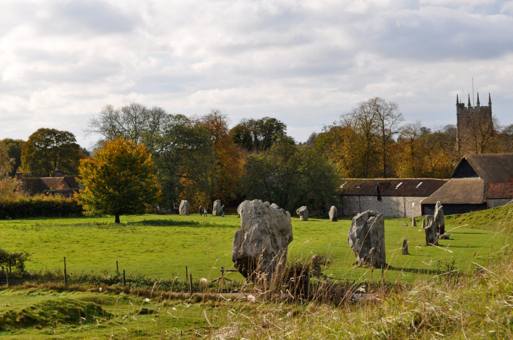 photograph of standing stones in a field, with church and buildings in background