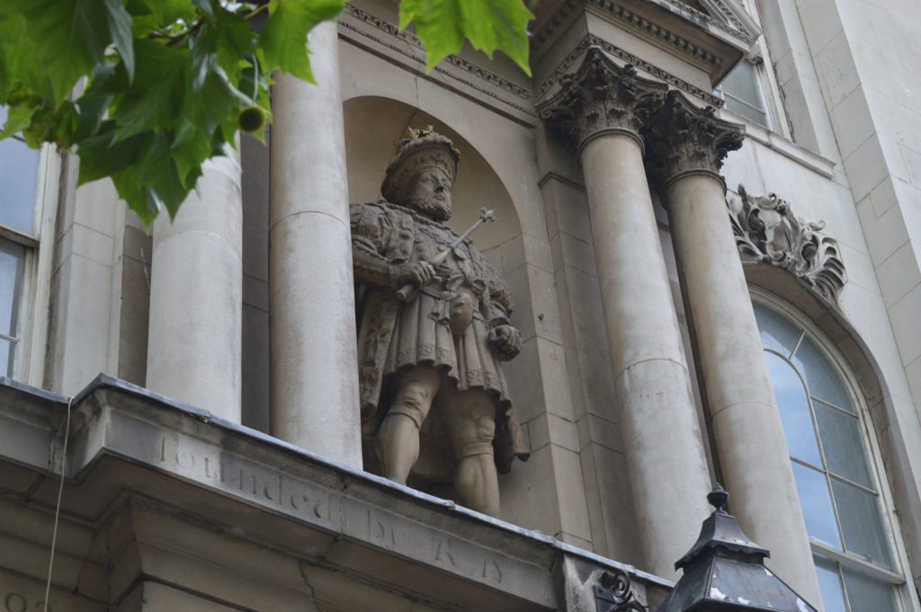 photogrpah of gateway to hospital with statue of henry viii