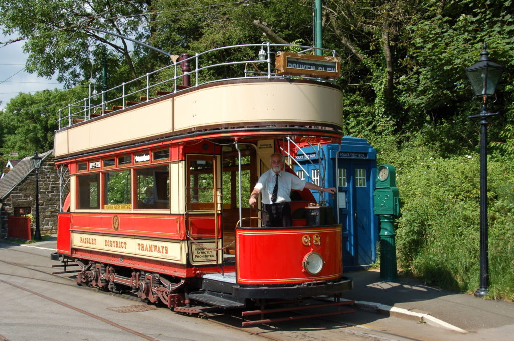 photograph of man driving red and cream tram