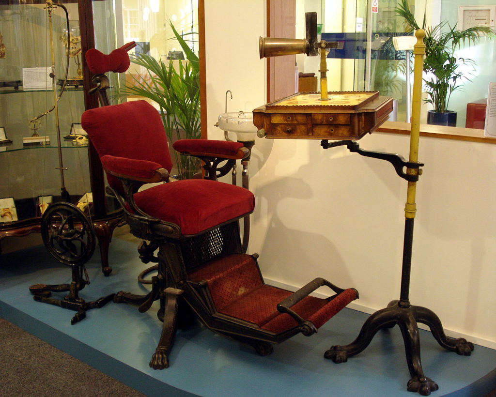 photograph of old dental examination chair in red velvet