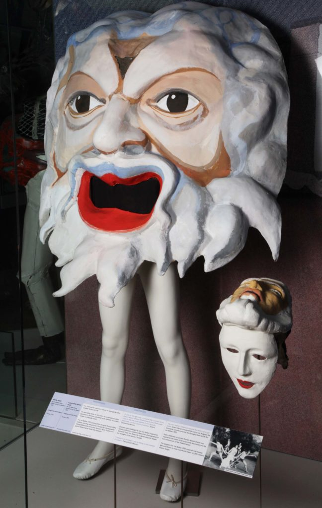 a photo of two theatrical masks in a museum display