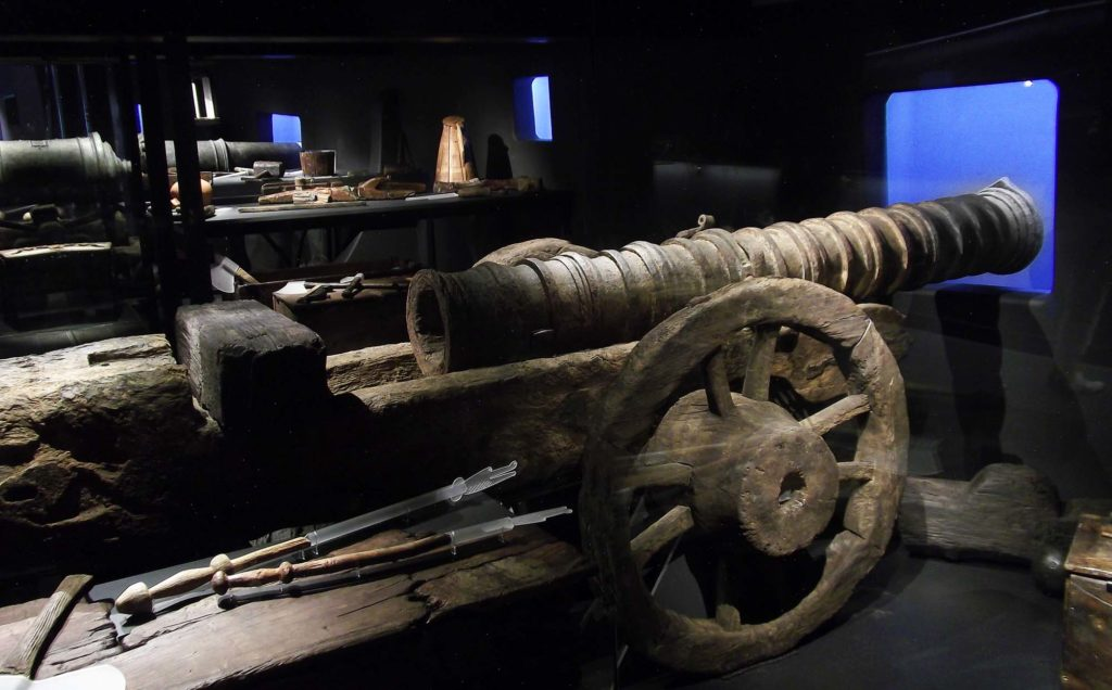 a photo of a large iron cannon in galley