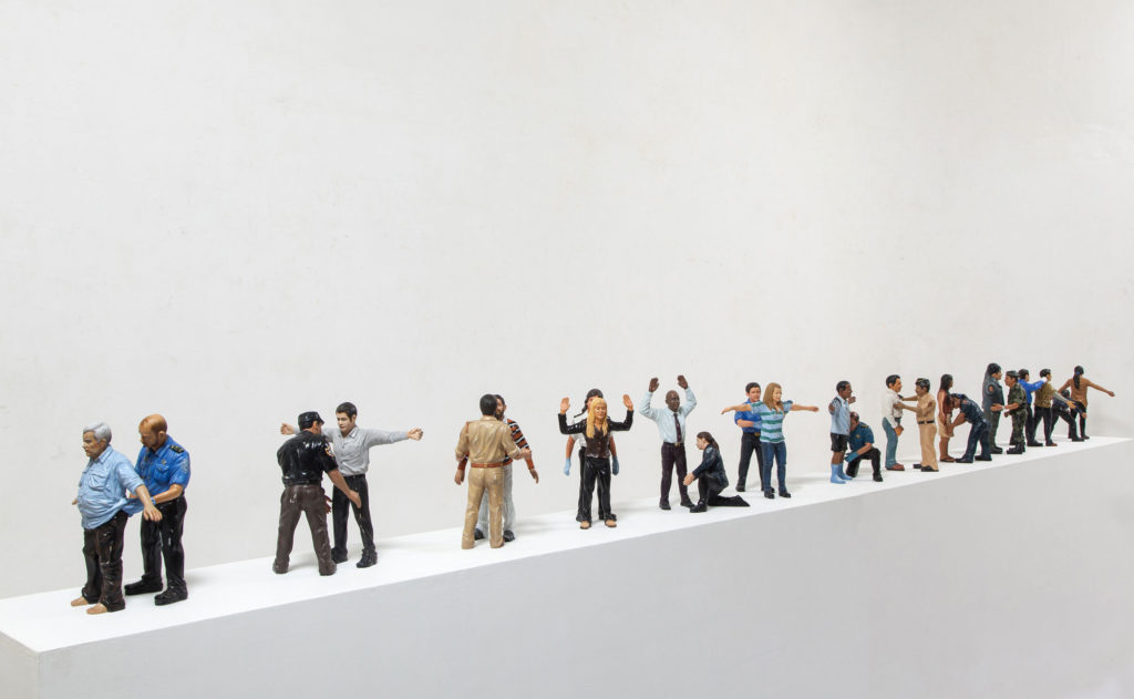 photograph of artwork showing miniature models of people standing in a line being searched