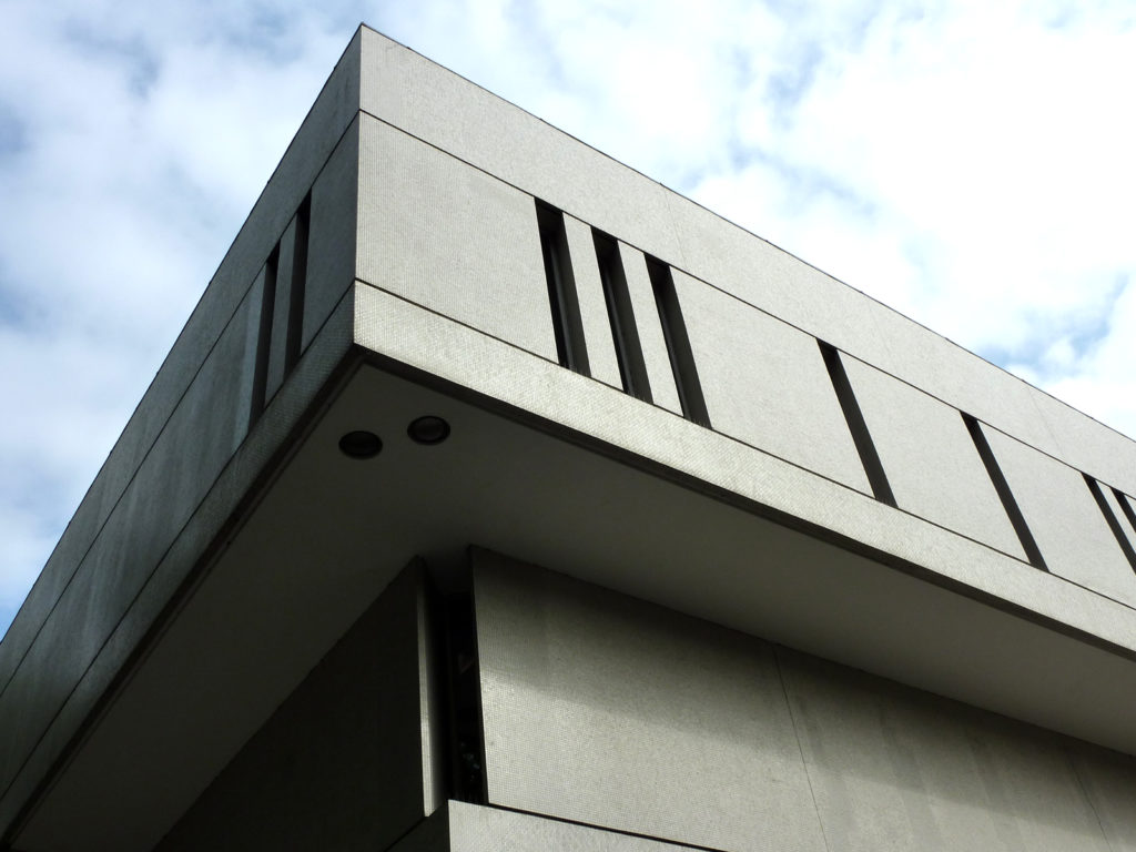 photograph of corner of modernist building against a blue cloudy sky