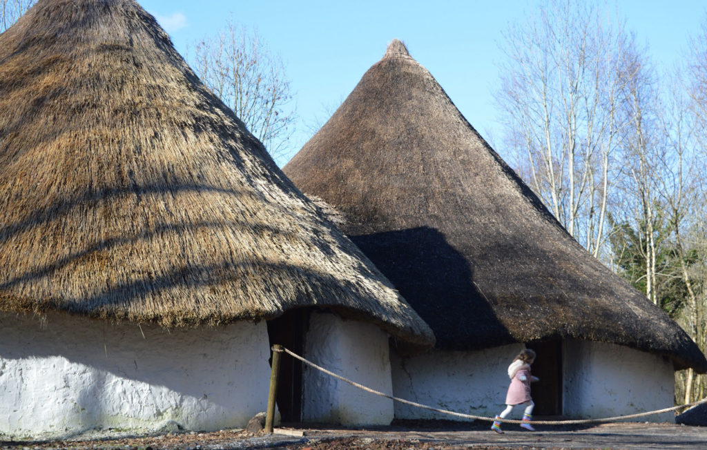 image of a child in front of a reconstructed Iron Age farmstead