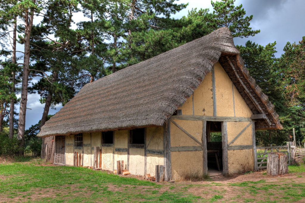 photogrpah of reconstructed ancient building with thatched roof