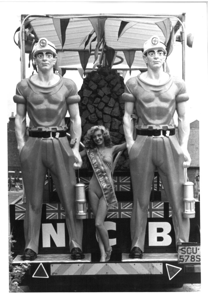 a balck and white photo of a woman in bikini posing between two large statues of muscled miners